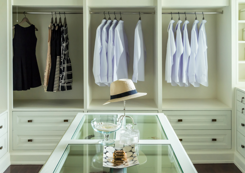 white hat and jewelry set on a dresser table in a walk in closet room.