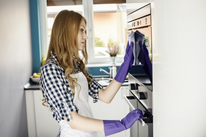Beautiful blonde woman cleaning with microfiber rag outside of microwave oven. On her hands protective rubber gloves.
