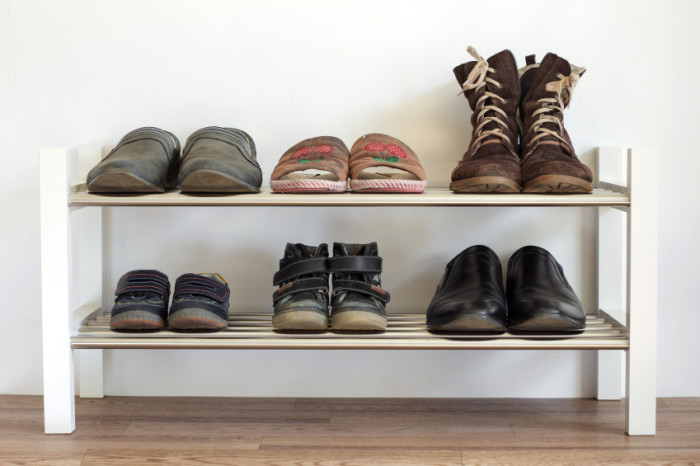 Six pairs of shoes on a shelf in the hallway in the house for the whole family: dad's, mama's and child.