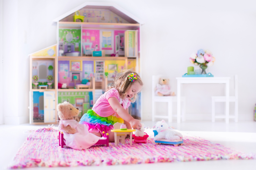 Little girl playing. Kids with doll house and stuffed animal toys. Children sit on a pink rug in a play room at home or kindergarten. Toddler kid with plush toy and dolls. Birthday party for little child.