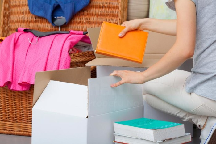 A woman packing colorful books into a cradboard box