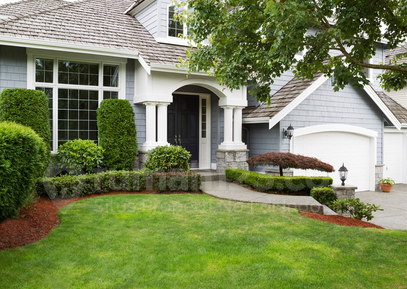 Newly painted exterior of a North American home during summertime with green grass and flower beds