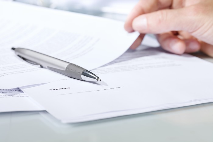 Close-up shot of a silver pen on a desk with documents and hand. Concept of business and agreement