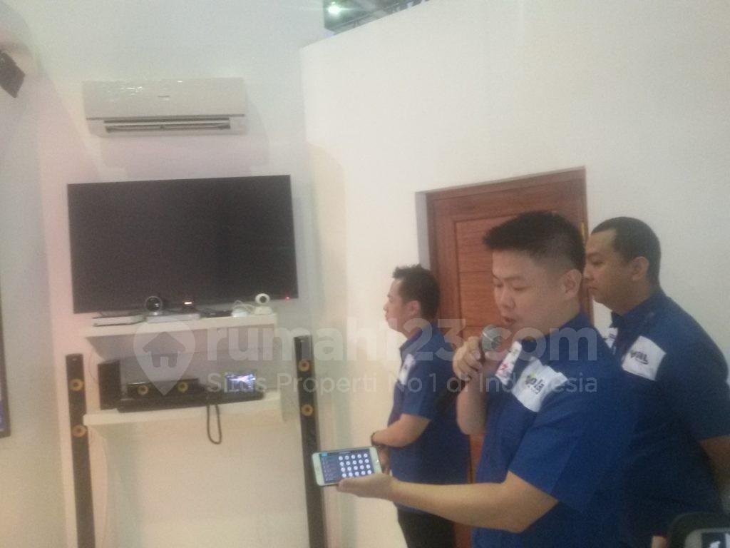 """CEO PT Berkat Inovasi Megah, Eric Cong (pegang ponsel) mempraktikkan penggunaan """"smart home control"""" di Jakarta Convention Center, Kamis (3/11). Foto: Rumah123/Ade Miranti."""