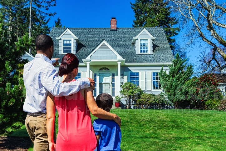 Photo of a young mixed-race family admiring a home - possibly their first home, or the home they hope to own.