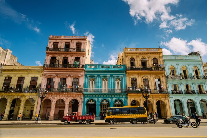 Havana, Cuba - November 6, 2015: Old apartment buildings in Old Havana, Cuba. Colourful facades of buildings facing Capitolio on Paseo Marti Boulevard. Rows of balconies with fresh laundry drying in the hot Caribbean Sun. Tenants outdoors, doing chores outside.Typical scene all around old Havana, where ever you see old buildings with people still living inside. Traffic and people on the street. Variety of colours and styles. Beauty of old architecture neglected over many years with out upkeep.