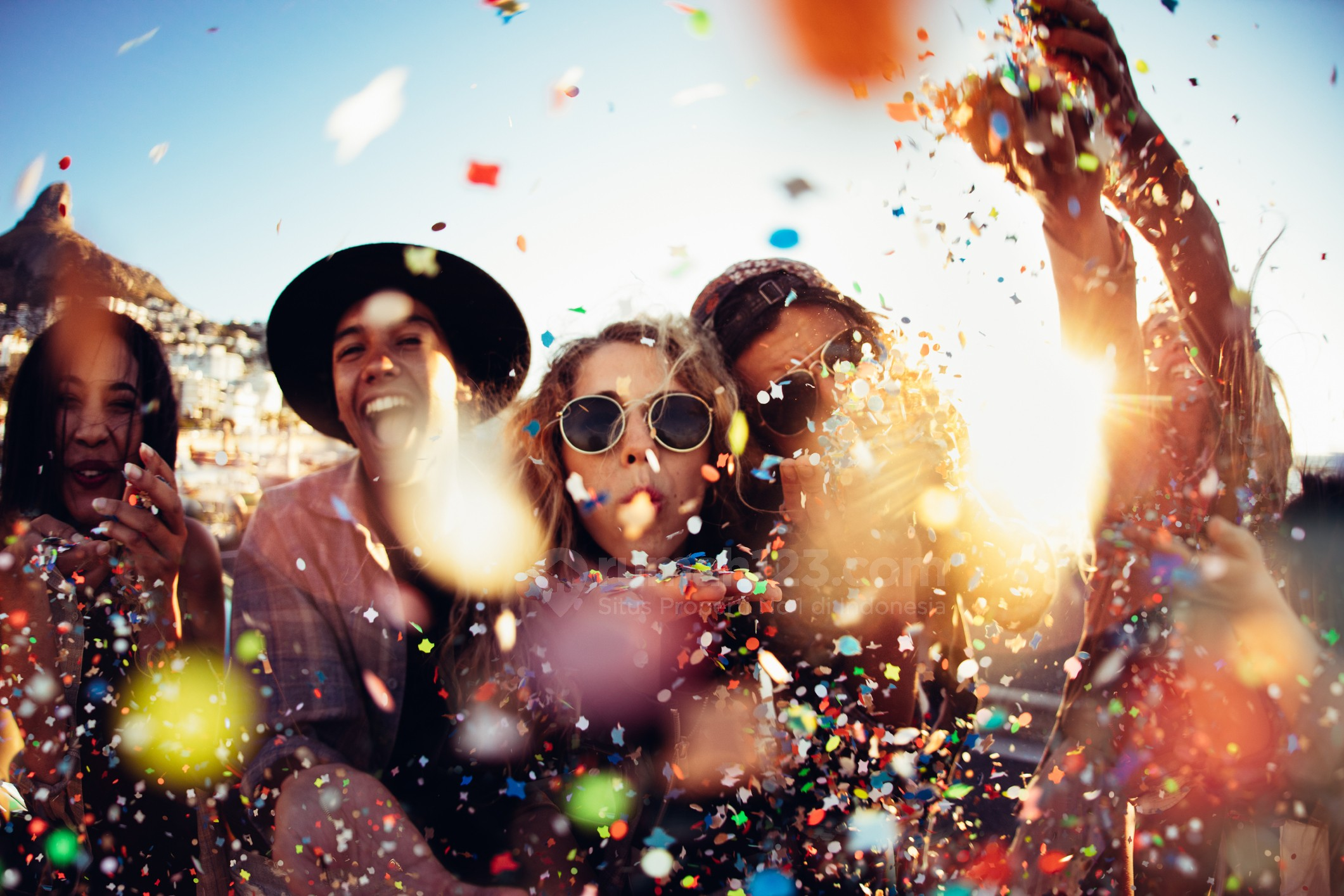 Group of teenager hipster friends partying by blowing and throwing colorful confetti from hands with sunset sun flare