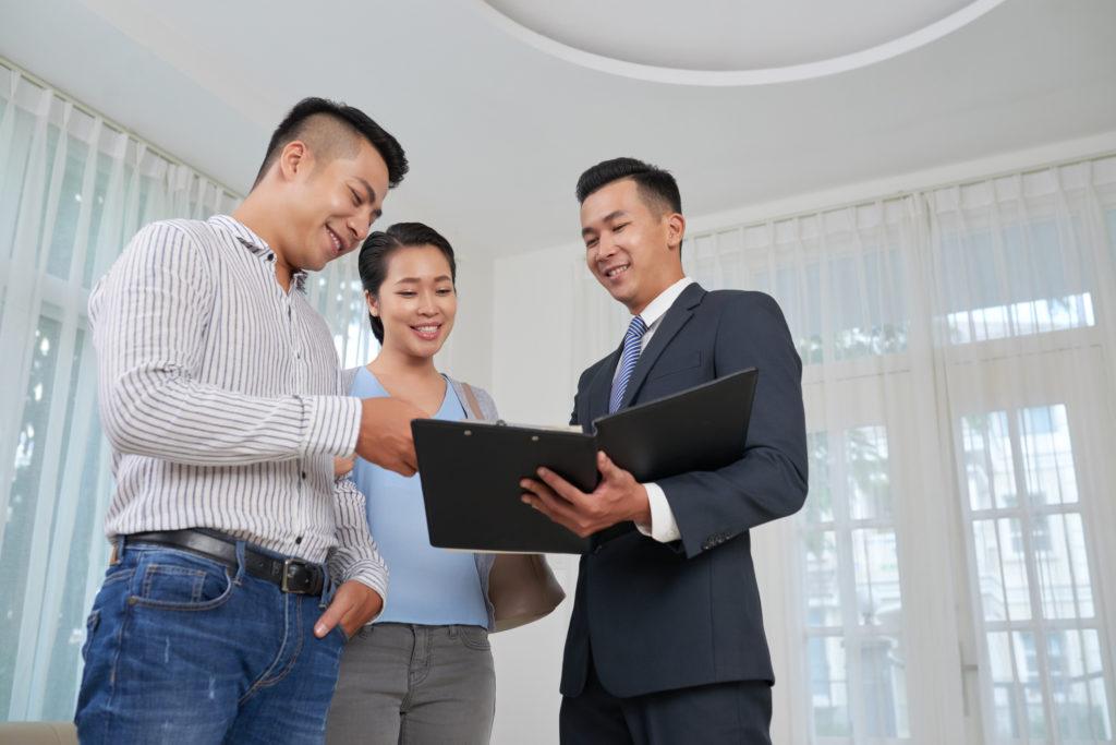 agen properti sedang memasarkan rumah yang dijual kepada pembeli - rumah123.com