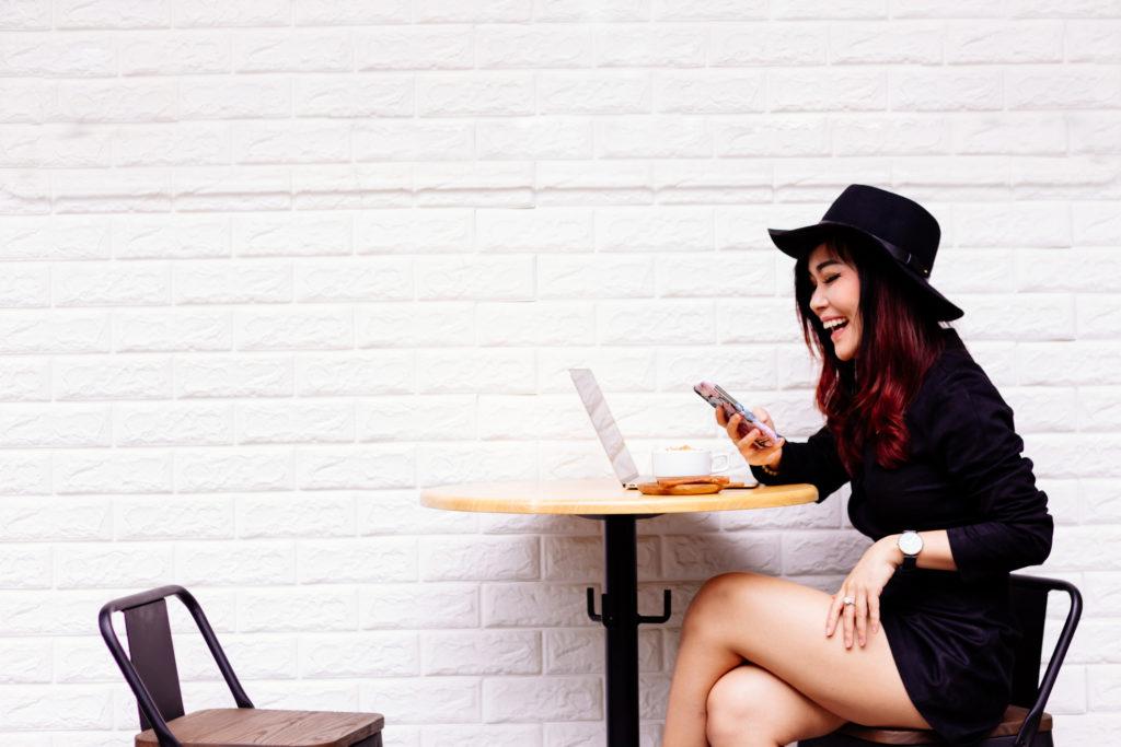Seorang perempuan duduk di samping dinding bata ekspos - Rumah123.com