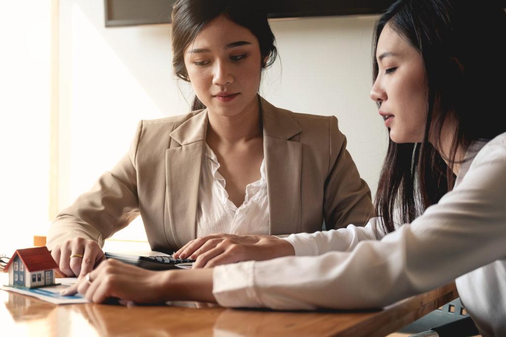 Penjual dan pembeli sedang menghitung pajak jual beli rumah - rumah123.com