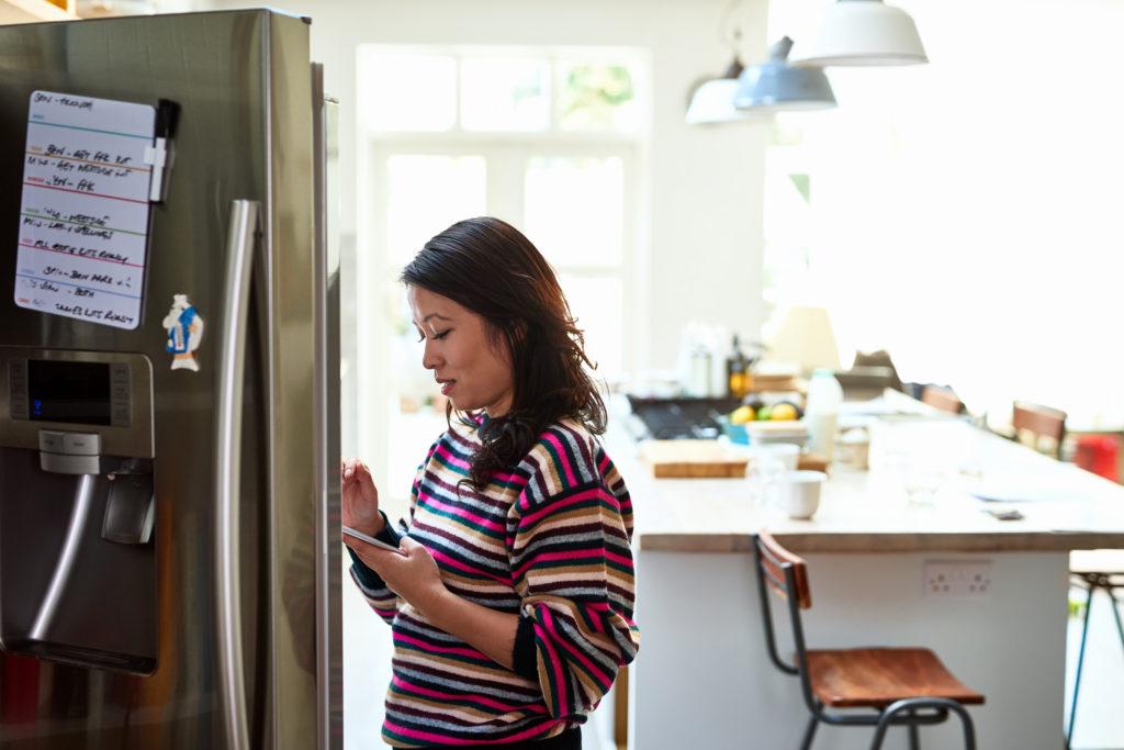 Seorang wanita mencari tahu bagaimana cara memperbaiki kulkas tidak dingin - Rumah123.com