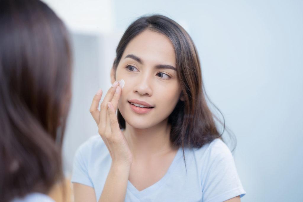 Seoran wanita sedang mengaplikasikan sunscreen ke wajahnya - Rumah123.com