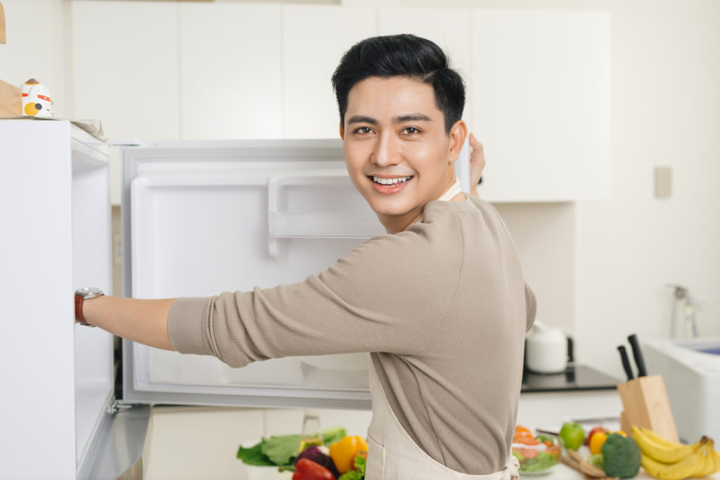 Seorang pria sedang membuka kulkas di rumahnya - Rumah123.com/Getty Images