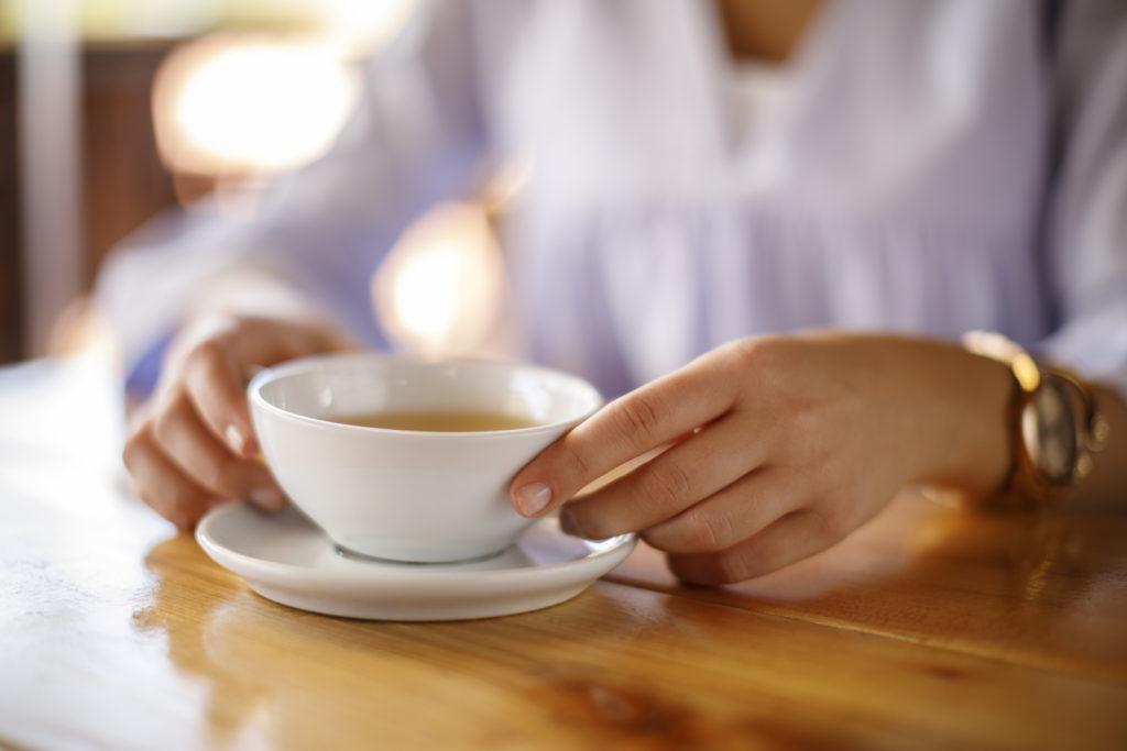 Ilustrasi seorang wanita sedang minum teh jati cina - Rumah123.com