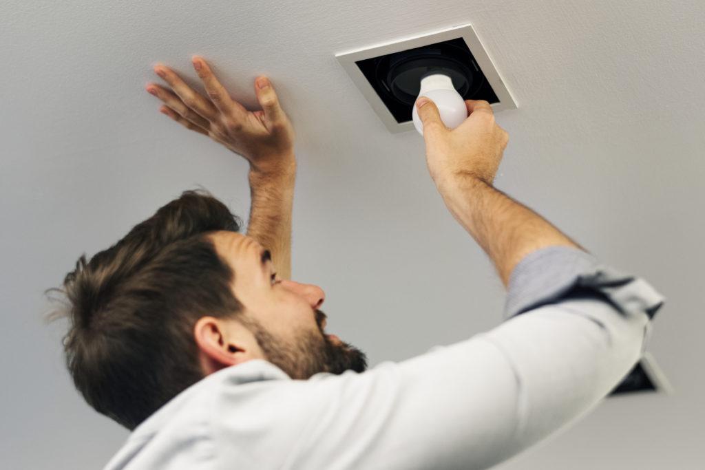 Seorang pria sedang memasang lampu LED rumah - Rumah123.com