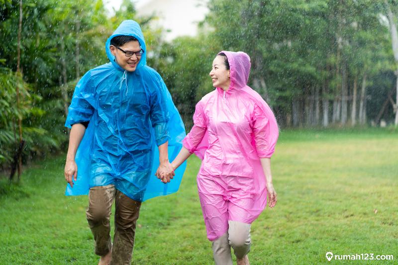 pasangan memakai jas hujan