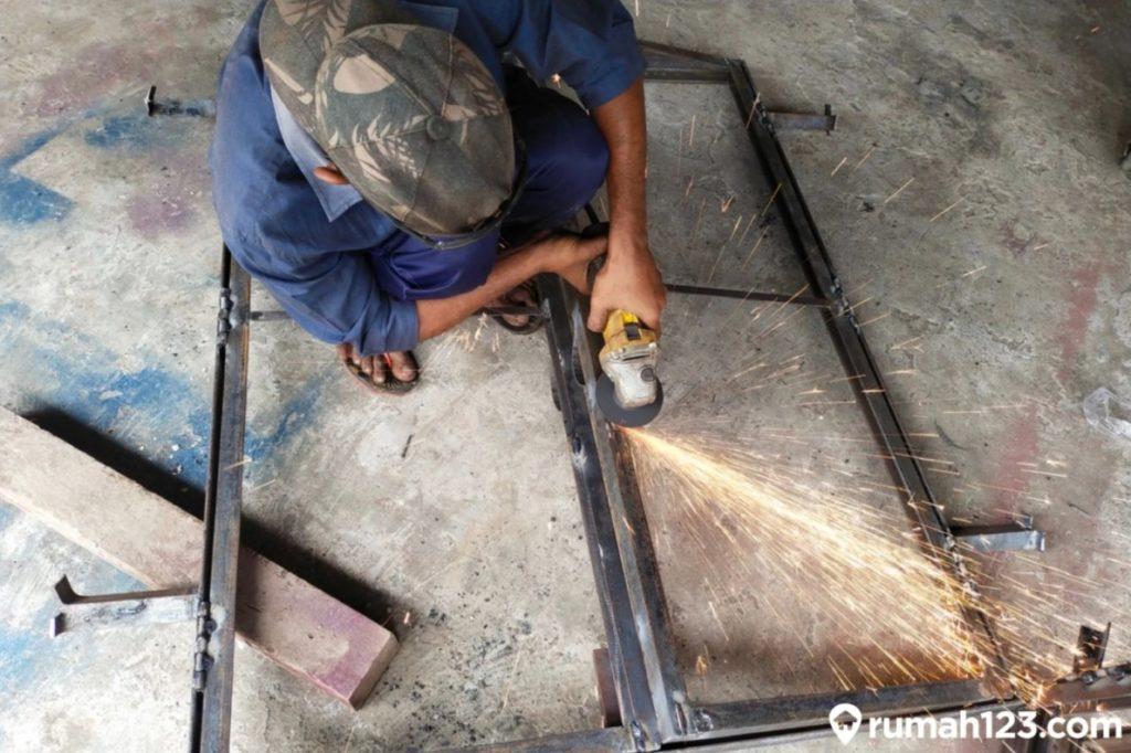 seorang tukang sedang membuat pagar rumah